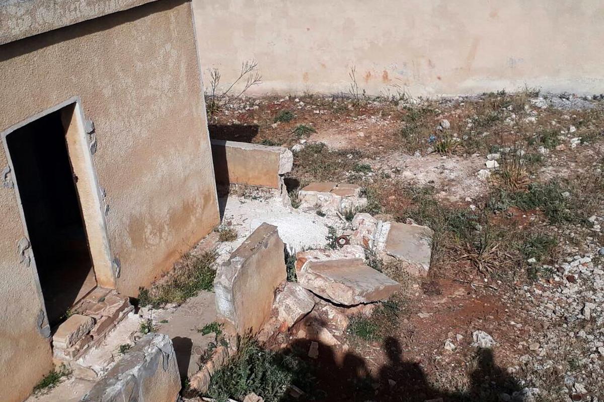 Trümmerteile einer Mauer versperren fast den Eingang eines verlassenen Schulgebäudes in Syrien