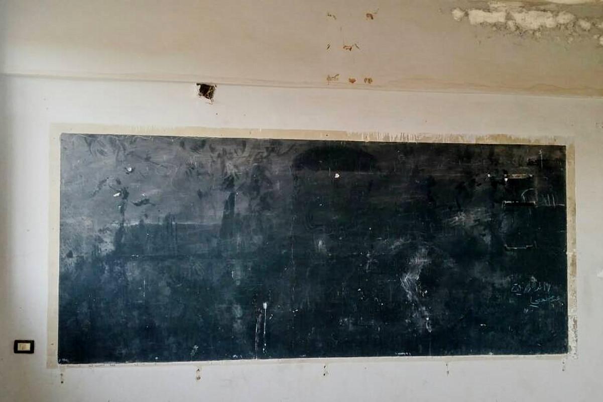 Eine schwarze Schultafel in den verlassenen Räumen einer ehemaligen Schule in Syrien.