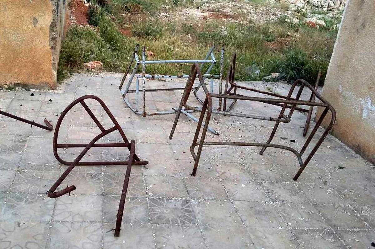Verrostete Gestelle von Schultischen und Stühlen liegen auf dem Hof einer ehemaligen Schule.