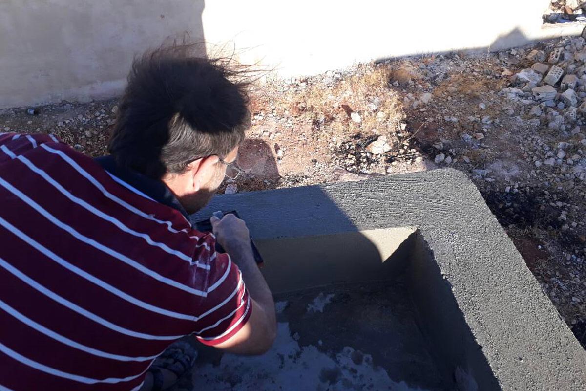 Ein Mann verputzt eine niedrige Mauer draußen vor der Schule.