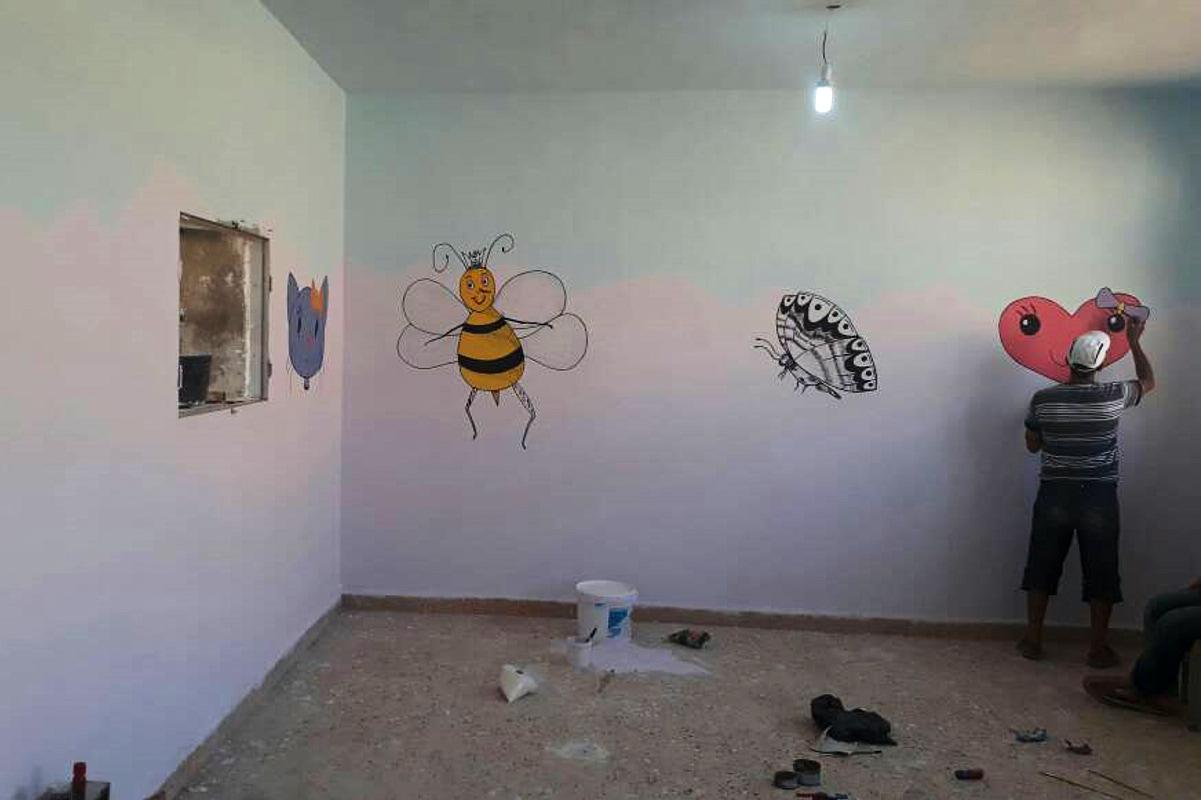 Ein Mann bemalt die renovierten Wände eines Klassenzimmers mit bunten Figuren.