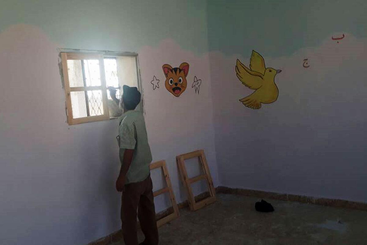 Ein Mann bringt neue Fensterläden aus Holz in einem Klassenzimmer an. An den Wänden sind Bilder von einer Katze und einem gelben Vogel.
