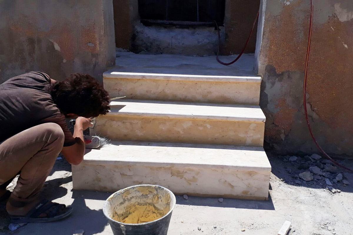 Ein Mann repariert die Treppenstufen am Angang der Schule. Im Vordergrund steht ein Eimer mit Mörtel.