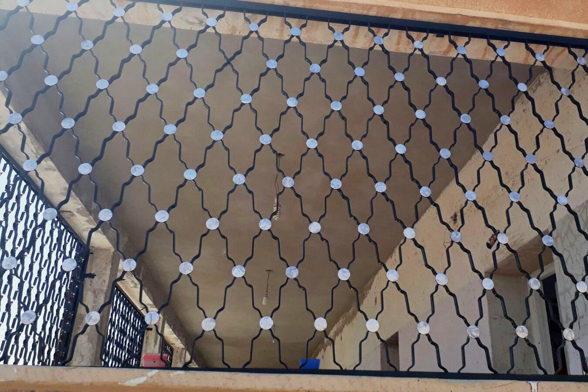 Dekorative, neu geschmiedete Gitter an den Fenstern.