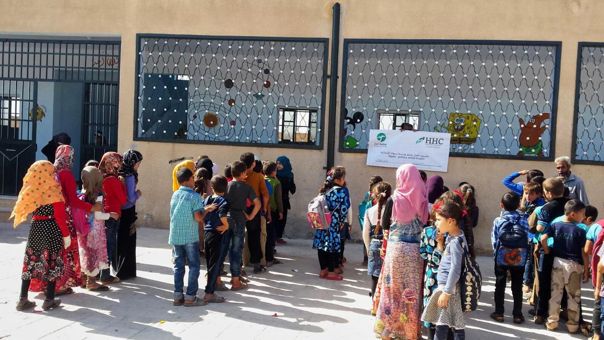 Kinder stehen in vier Reihen vor einem braunen Schulgebäude mit großen Fenstern. Rechts sieht man einen älteren Mann mit Bart. Die Kinder tragen bunte Kleidung. Einige Mädchen tragen Kopftücher.