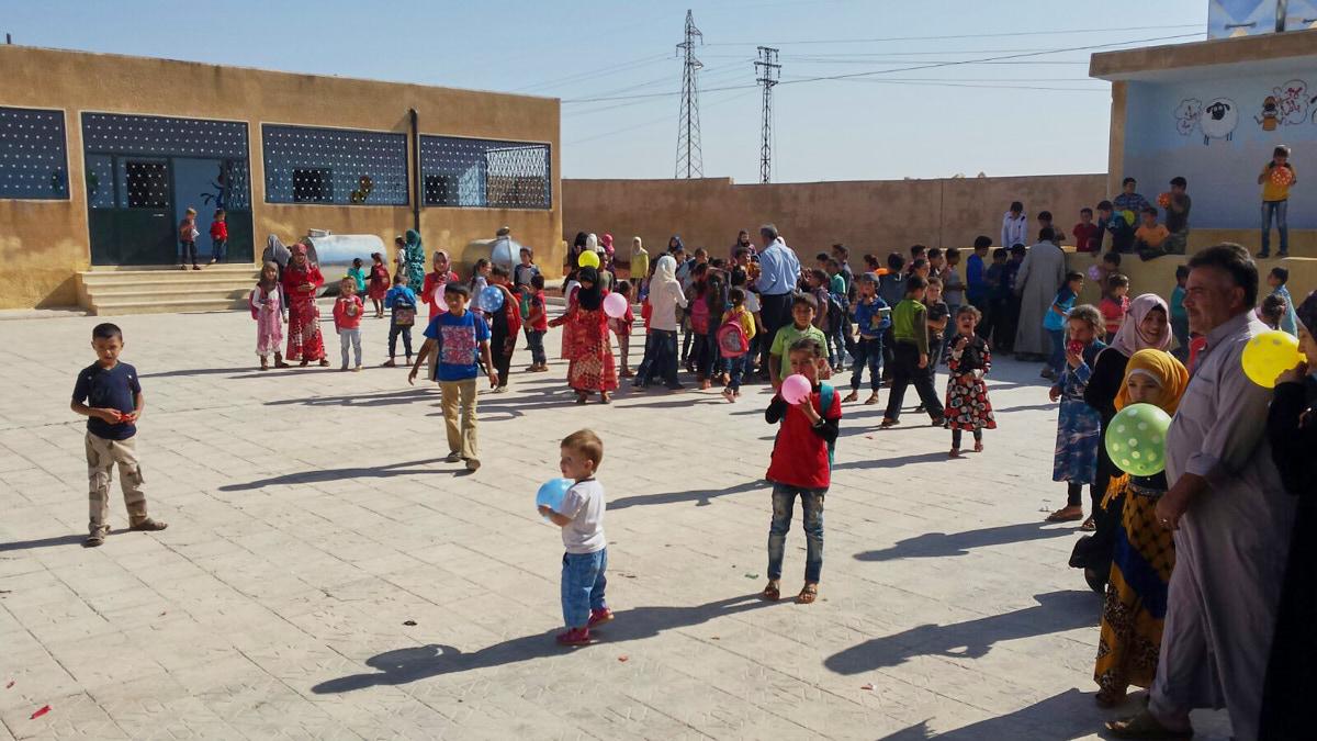 Kinder spielen draußen im Hof einer Schule. Einige haben bunten Luftballons. Man sieht auch einige Erwachsene. Hinten sieht man das renovierte braune Schulgebäude.