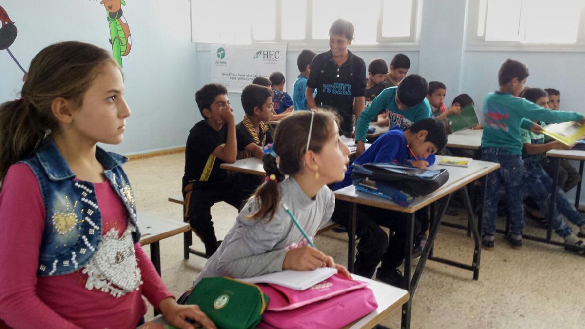 Kinder in einem Klassenraum. Vorn sitzen zwei Mädchen. Sie schauen konzentriert nach rechts. Hinten sitzt eine Gruppe Jungen an Tischen. Sie schreiben oder sprechen miteinander.