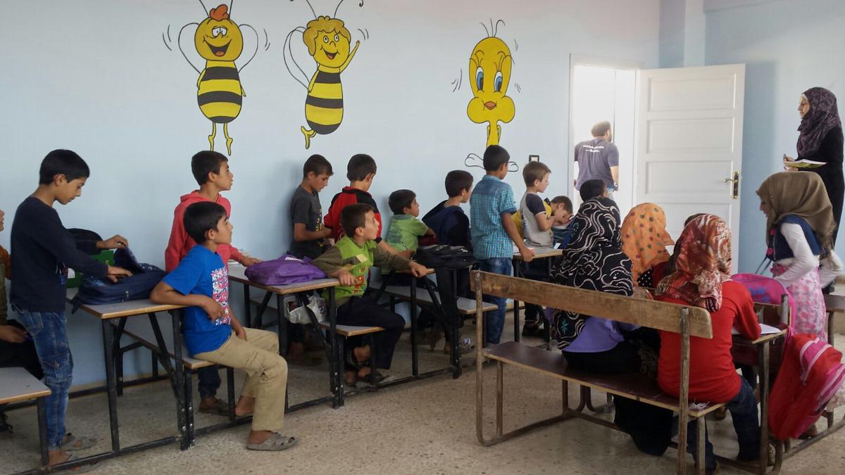Eine Gruppe Mädchen und Jungen sitzt in einem Klassenraum. Rechts steht eine Frau mit Kopftuch. Auf die Wand sind Cartoonfiguren gemalt: Bienen und ein gelber Vogel.