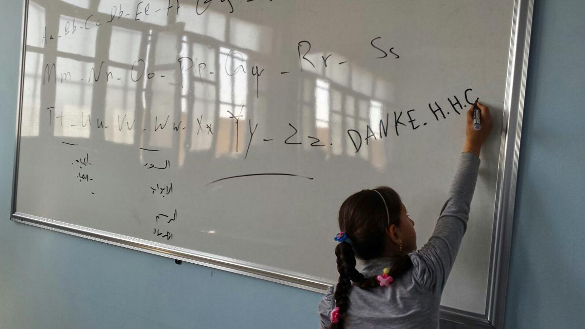 """Ein Mädchen schreibt """"DANKE HHC"""" an eine weiße Tafel. Die hellen Fenster des Klassenraums spiegeln sich in der Tafel."""