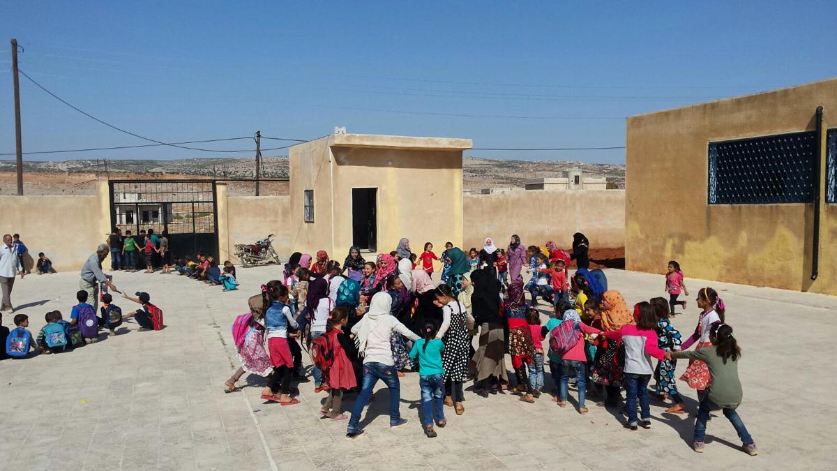 Kinder spielen draußen im Hof einer Schule. Sie fassen sich an den Händen. Hinten sieht man zwei grau-braune Gebäude und ein großes Tor.