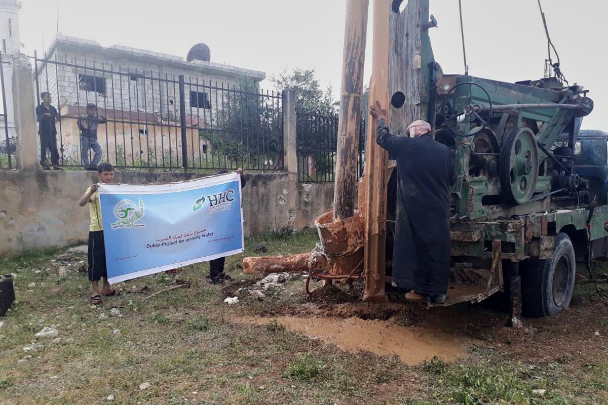 Ein Mann steht hinten auf einem großen Brunnenbohrfahrzeug. Daneben halten zwei Jungen ein Schild mit dem HHC-Logo hoch.