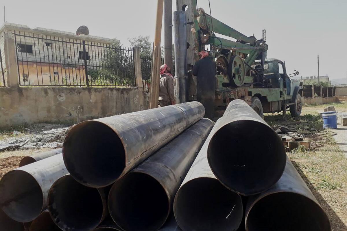 Große Rohrleitungen aus Stahl liegen auf einem Stapel. Dahinter sieht man ein Brunnenbohrgerät.