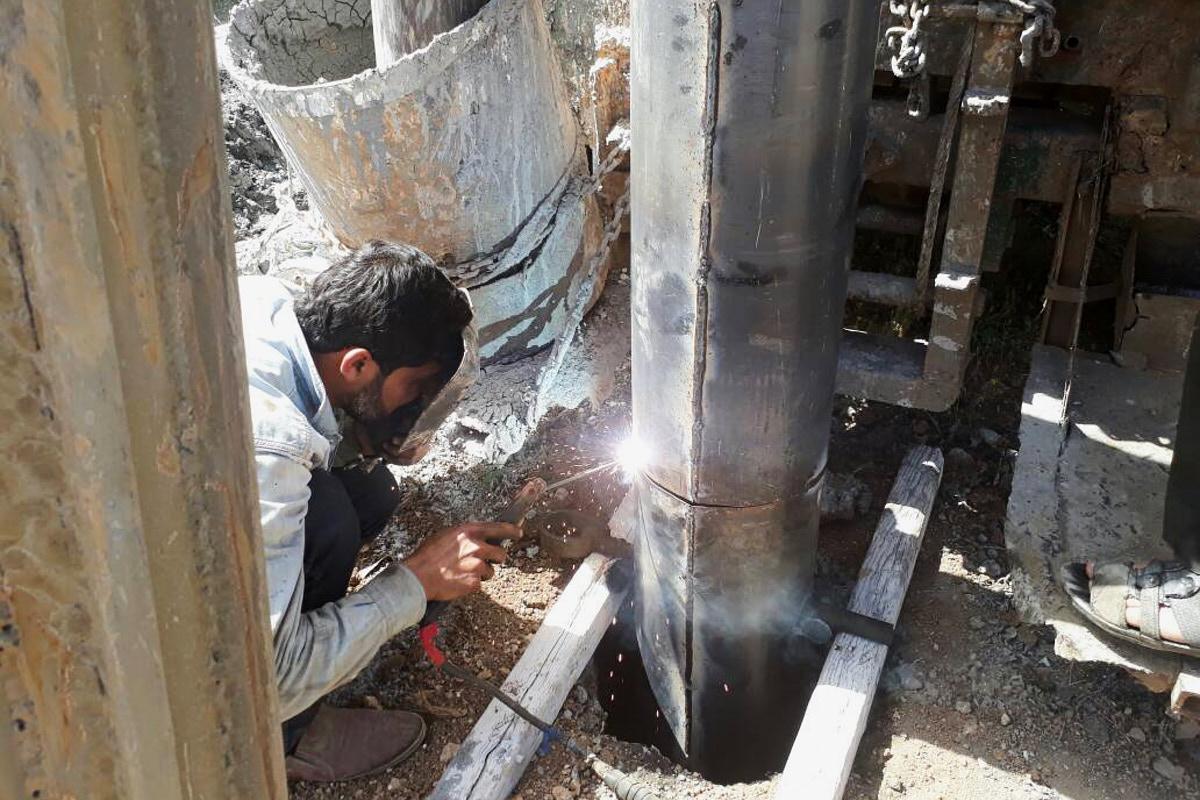 Ein Mann hockt auf dem Boden und schweißt eine dicke Rohrleitung, die aus der Erde ragt.