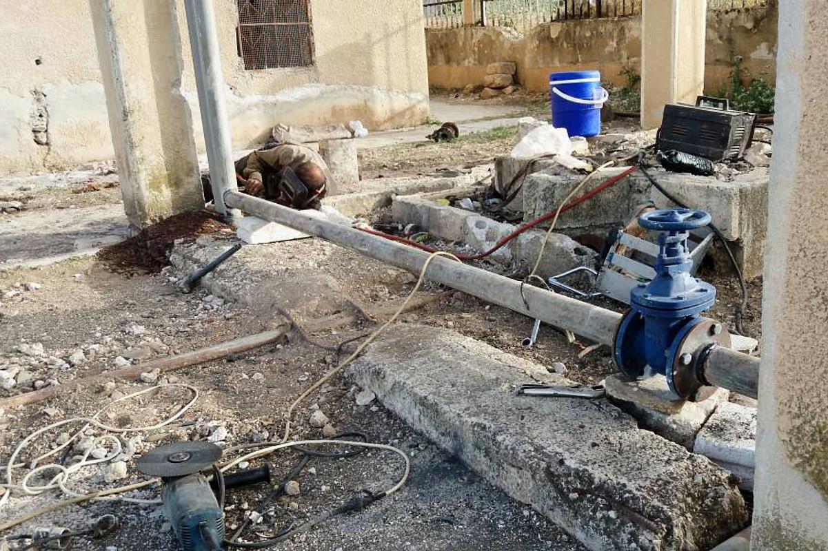Ein Mann montiert eine Rohrleitung. Vorn hat die Leitung in großes blaues Ventil.