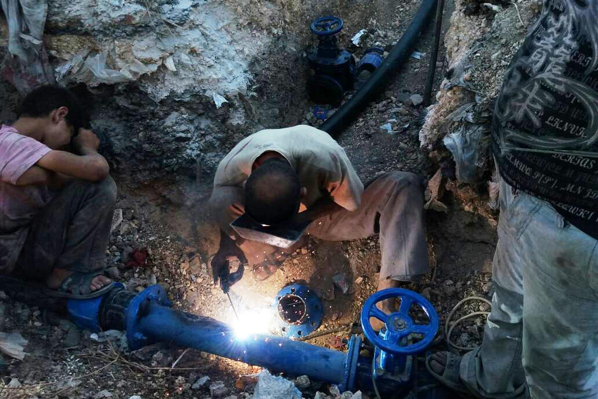 Zwei Männer arbeiten an einem Brunnen. Einer schweißt an einer blauen Rohrleitung.